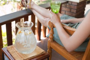 Attractive Young Woman Relaxing on Porch of American Craftsman Style House with Glass and Pitcher of Ice Water, Detail