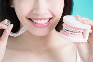 woman holding invisalign and braces