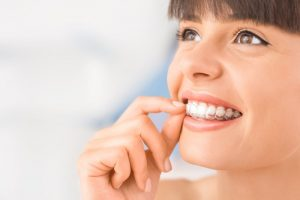 attractive young woman smiling inserting Invisalign in richmond